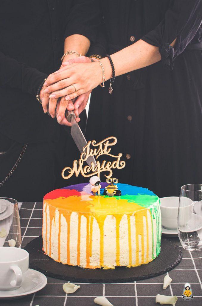 Anschneiden einer Hochzeitstorte als Rainbow Drip Cake